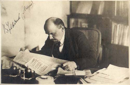 Lenin reads Pravda newspaper at his study desk at his flat in the Kremlin. October 16, 1918.