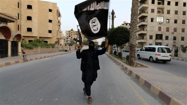 IS extremist brandishing the group's flag and a weapon in Raqqa, Syria. 2014. (Ogbodo Solution/ Flickr Creative Commons)