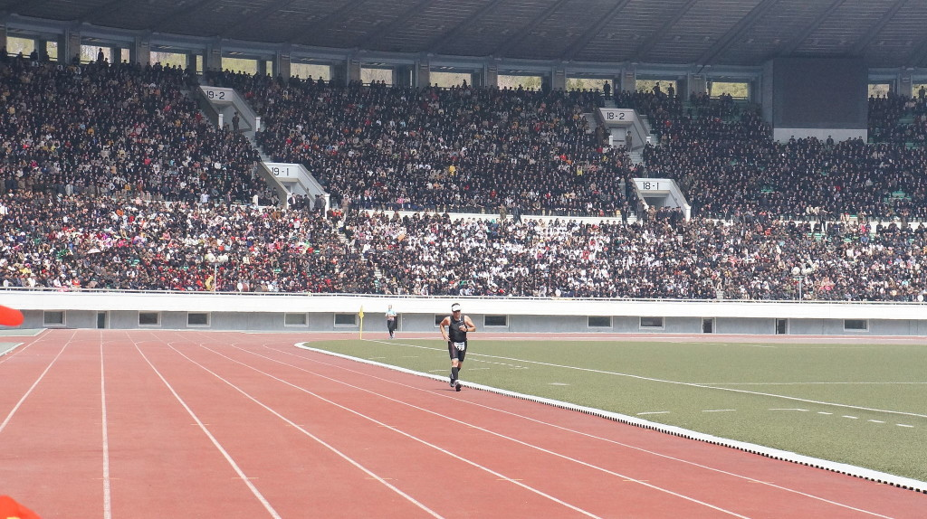 A runner enters a full stadium to finish the final lap of the 2014 Pyongyang Marathon. April 13, 2014 (Uri Tours/Wikimedia Commons)