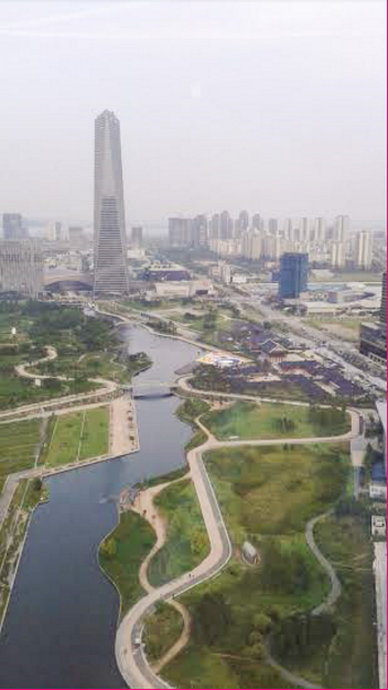 A picture of Central Park, the North East Asian Trade Tower and the surrounding buildings. The canal is composed of salt water from the ocean in order to be sustainable. August 17, 2015. (Personal image).