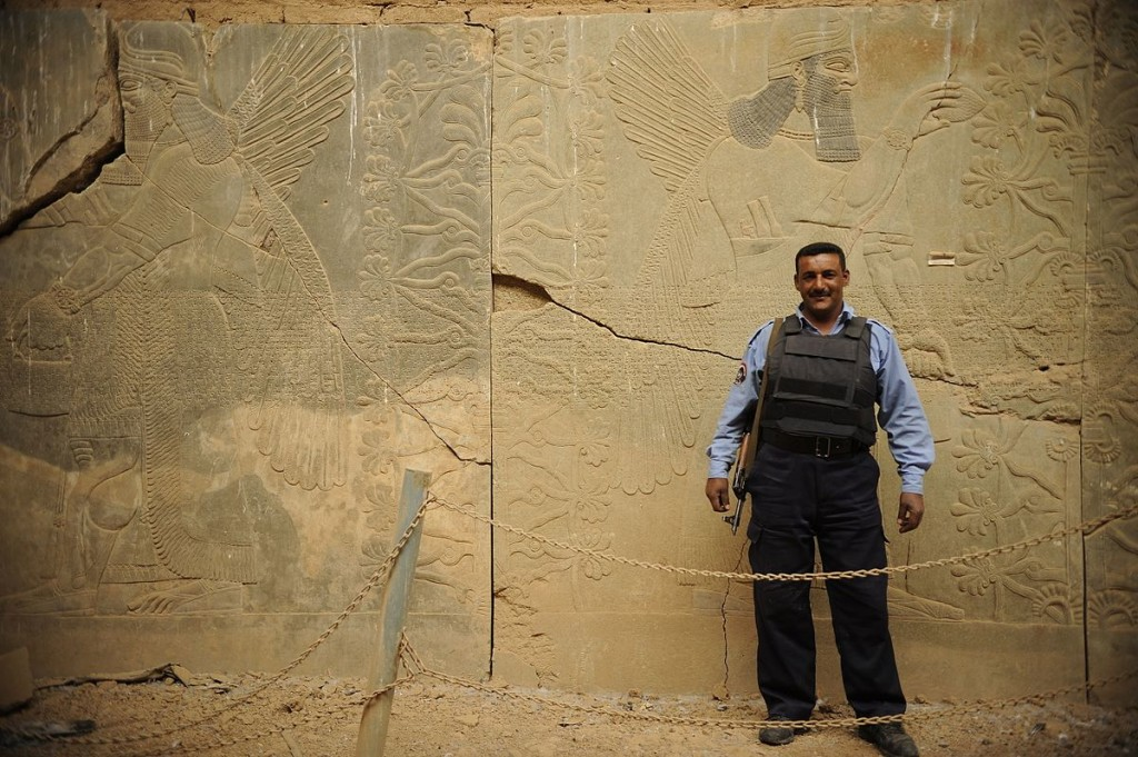 An Iraqi Policeman stands by a Nimrud wall relief that was protected by UNESCO prior to its destruction. 2008. (JoAnn Makinano/Wikimedia Commons)