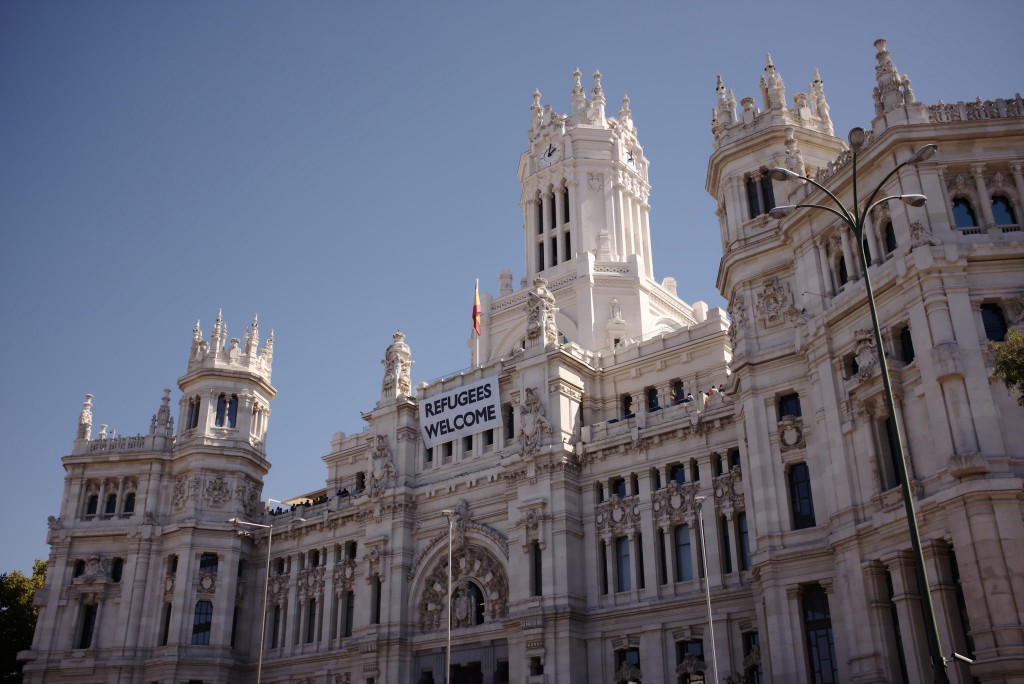 "The ""Refugees Welcome"" sign hangs from the Madrid City Hall to express solidarity with the millions of refugees leaving their country of origin in hopes of finding a home in Western Europe. Unfortunately, Spain has not been truly accepting of refugees and more specifically, of Muslim refugees and descendents. (Nicolas Vigier, Flickr)"