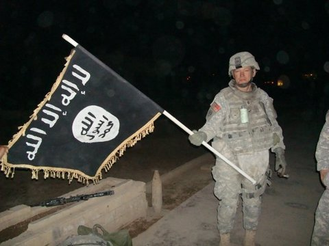 US Soldier holding a captured Islamic State flag. 2010. (US Army, Wikipedia Commons)