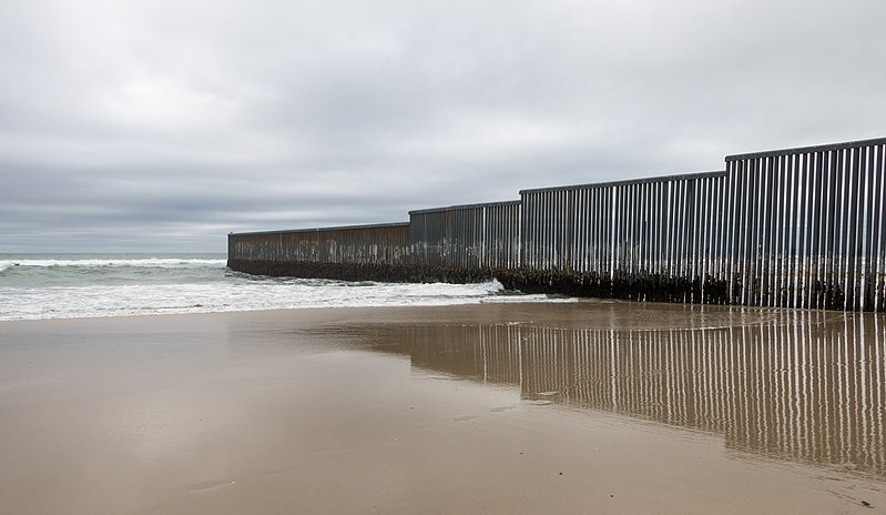 A cloudy day over where the U.S.- Mexico border meets the ocean in Tijuana, Mx. 2017. (Tomas Castelazo / Wikimedia Commons)