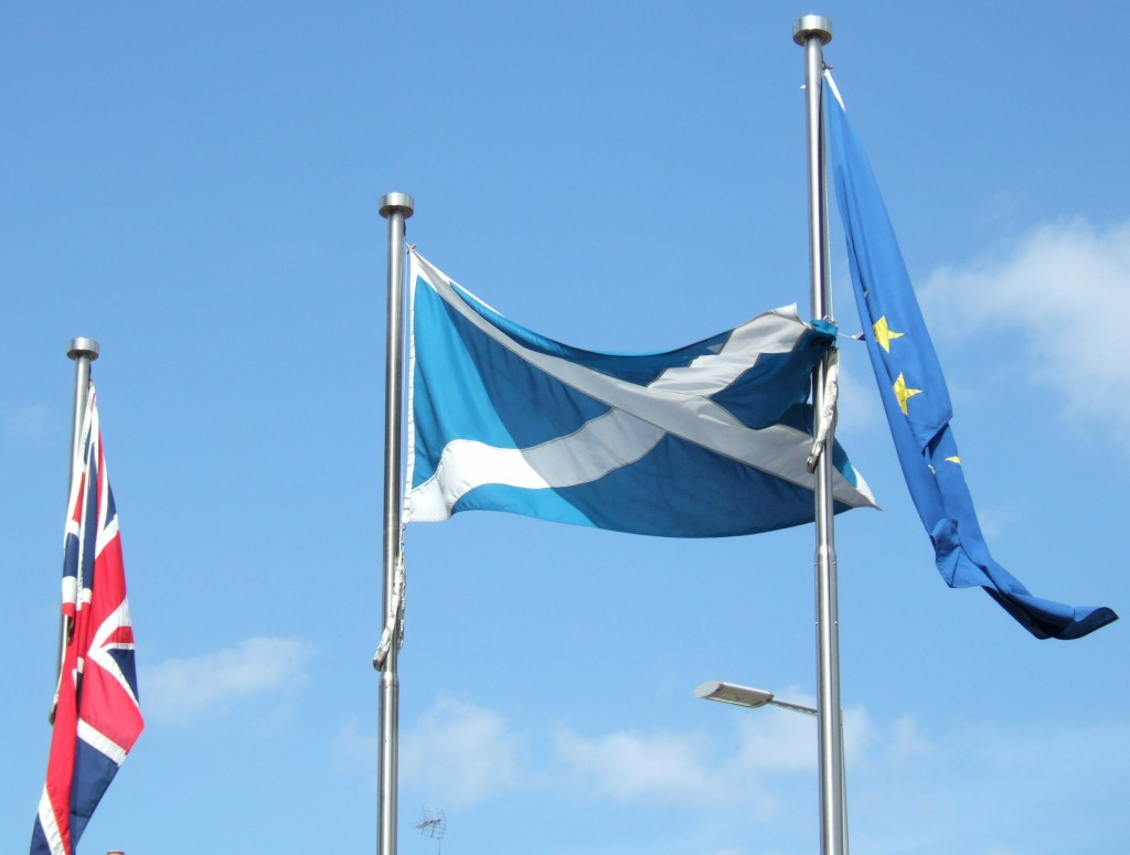 """Flags fly outside the Scottish Parliament in Edinburgh, Scotland. Which will remain after Thursday's vote? """" (Calum Hutchinson/Wikimedia Commons)"""
