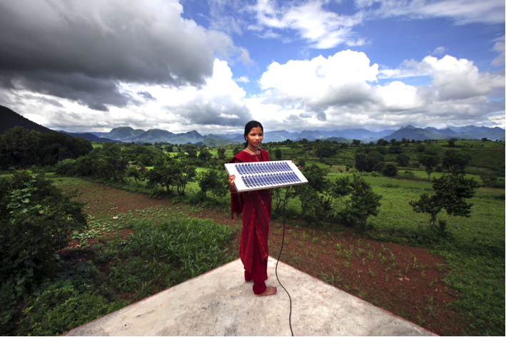 A young female engineer holds up a solar panel against the landscape of her home in Orissa, India.  (UK Department for International Development / Flickr Creative Commons)