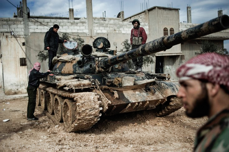 A Free Syrian Army member prepares to fight with a likely Russian-made tank whose crew defected from government forces (Freedom House/Flickr Creative Commons).