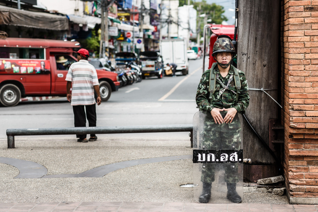 A soldier stands guard on a street corner in Bangkok in June 2014, a month after Thailand's most recent military coup (Tore Bustad, Flickr Creative Commons).