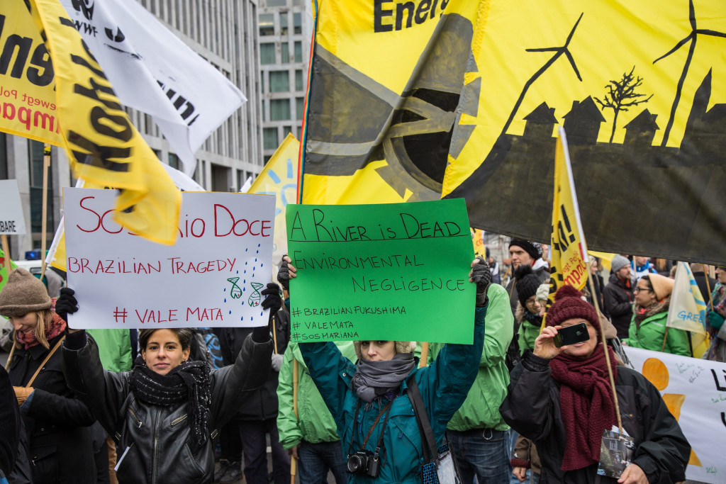 Caption: Greenpeace and other activist groups protestors at the Global Climate March in Berlin display anger over the burst dam in Minas Gerais, Brazil. November 29, 2015. (mw238/Flickr Creative Commons).