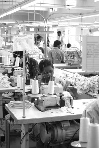 A worker in Tirapur, India sews finished fabric into baby shirts. (Communistpartyusa/Flickr), 2000.